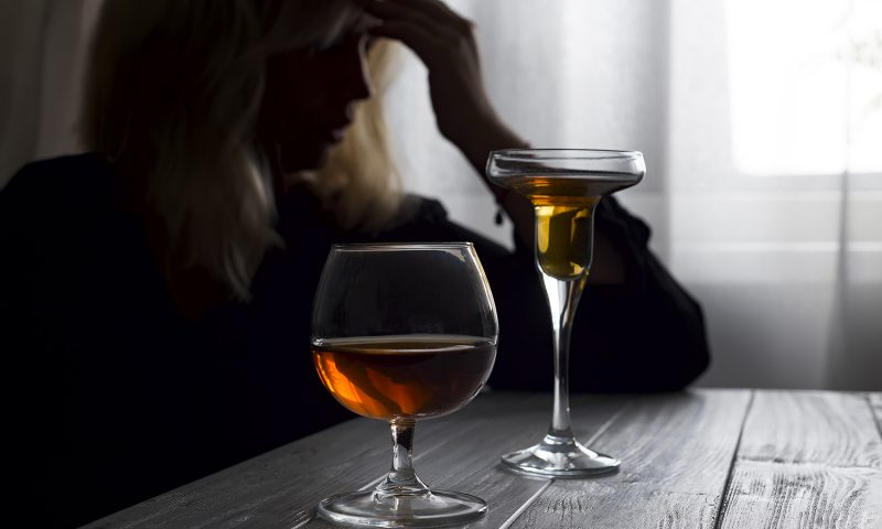 silhouette of anonymous alcoholic woman person drinking behind glass of alcohol. Alcohol addiction and Social problem - with alcoholism and poisoning