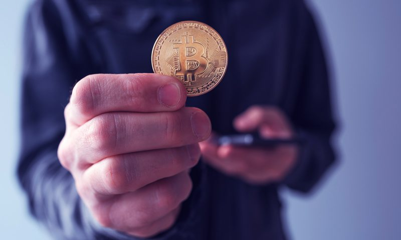 Man showing Bitcoin, close up of hands with BTC cryptocurrency coin