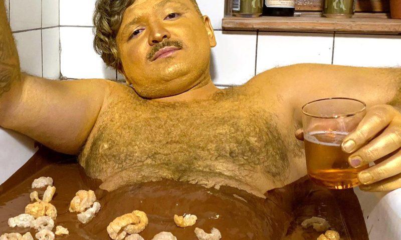 Umut Sakarya i et badekar af brun sovs, med flæskesvær, Fernet guldbajer og guldstøv. PR Foto